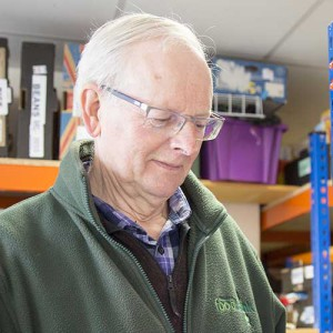 A male foodbank volunteer with office shelves in the background