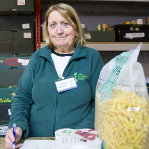 A female foodbank volunteer with a large bag of pasta