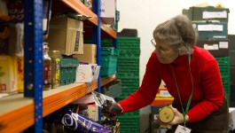 Volunteer stacks shelves at a foodbank in the Northeast
